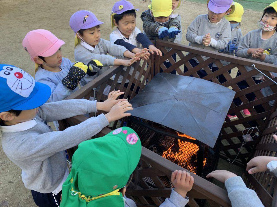 園庭で焚火を楽しむ園児