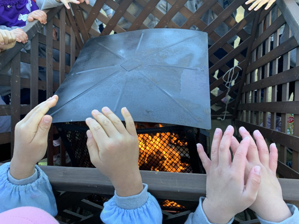 焚火にあたる子どもの手