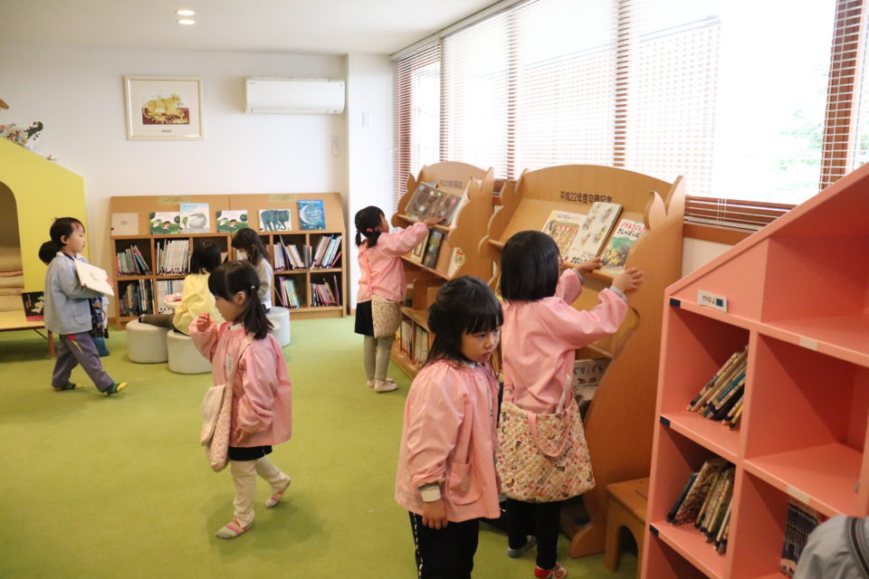 図書室で絵本を選ぶ園児達