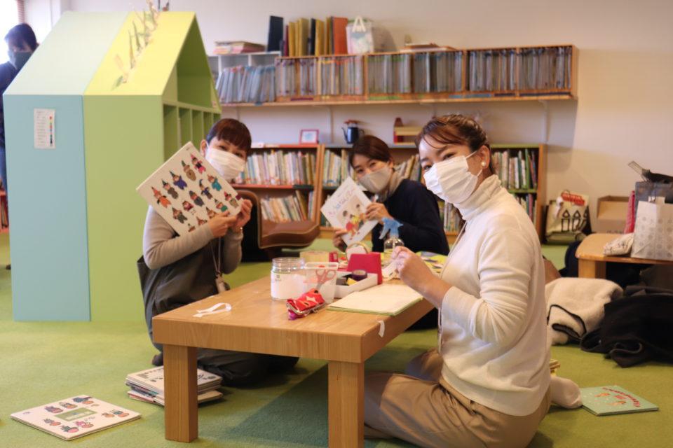幼稚園の絵本の修理をする保護者