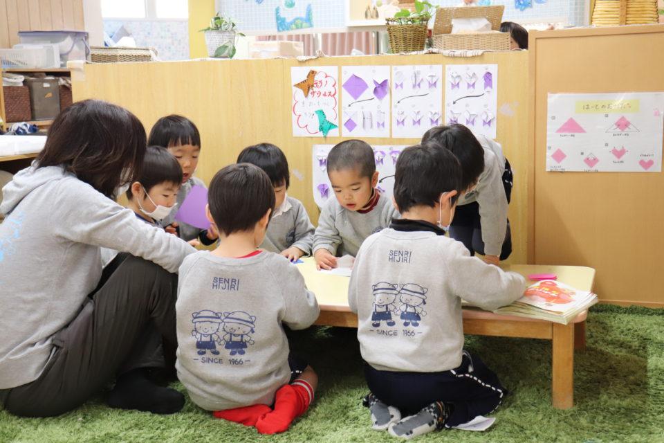 ホームクラスで折り紙をしている園児と先生
