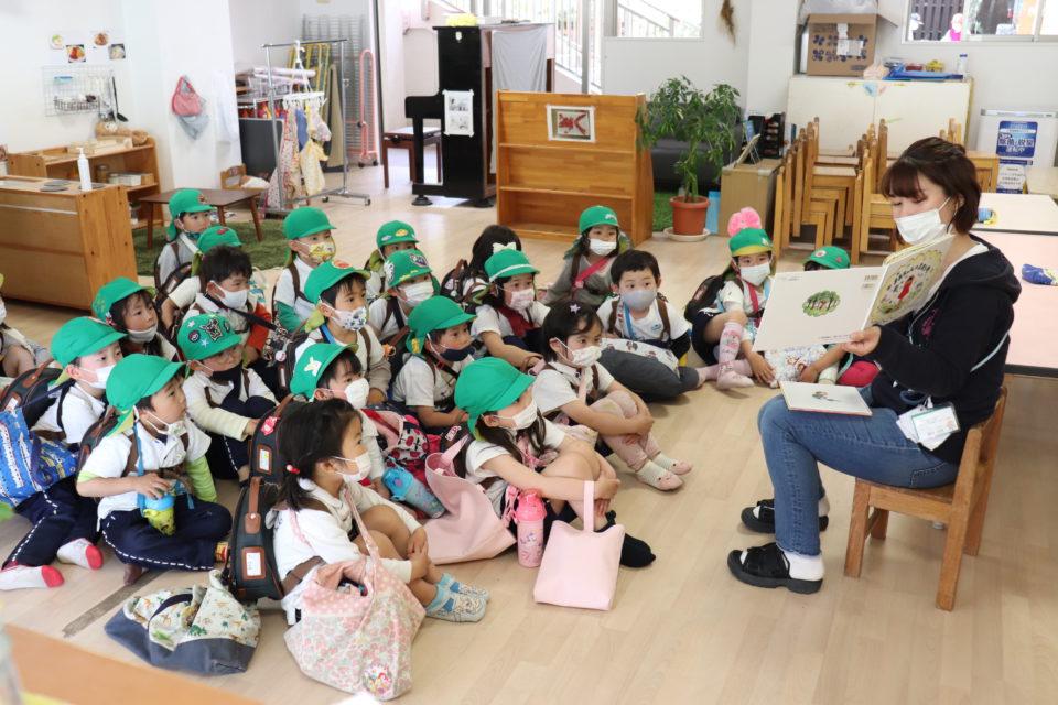 保育室で絵本を読んでもらっている園児達