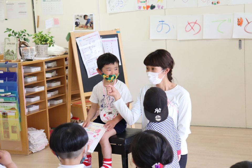 保育室でインタビューをしている先生と園児