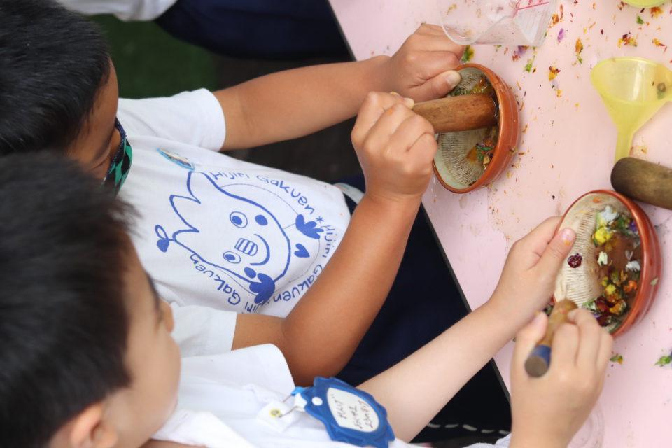 花を潰して色水遊びをしている園児達