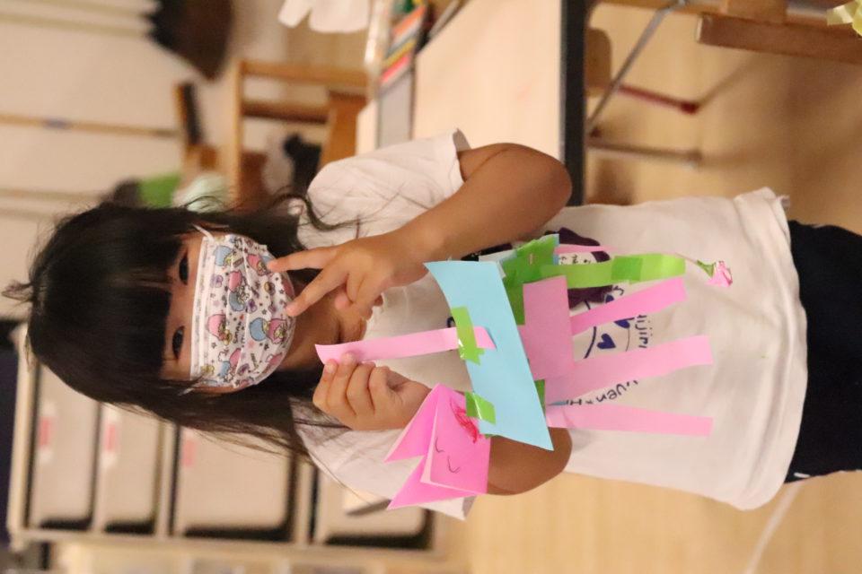折り紙の製作物を見せている女の子