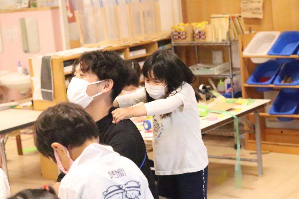 先生の肩もみをしている園児
