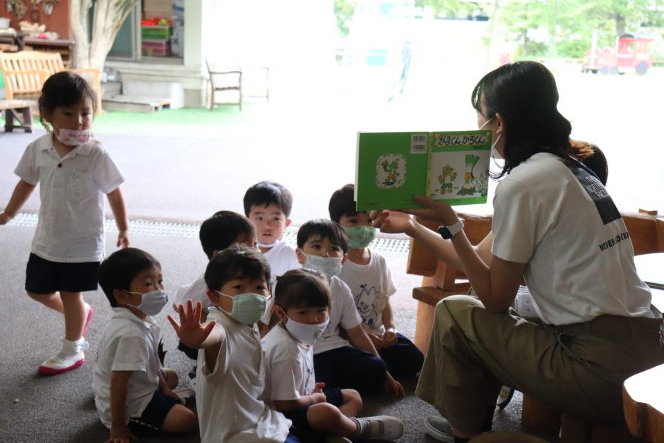 外で紙芝居を読んでもらっている園児達